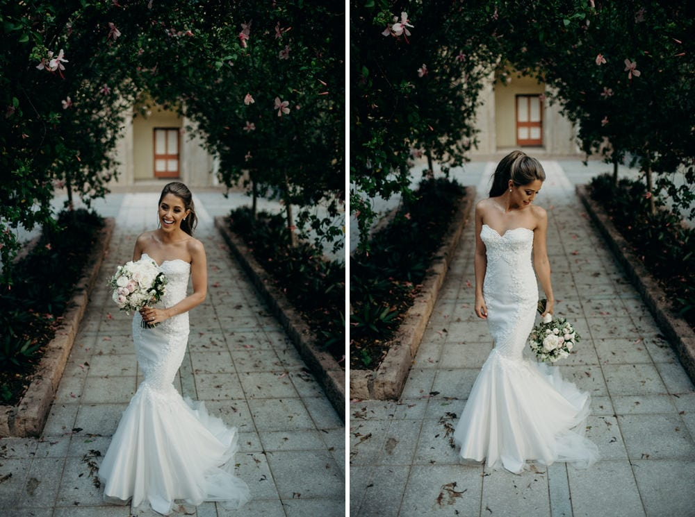 Bride under an arbour of flowers at All Hallows Brisbane by Cloud Catcher Studio