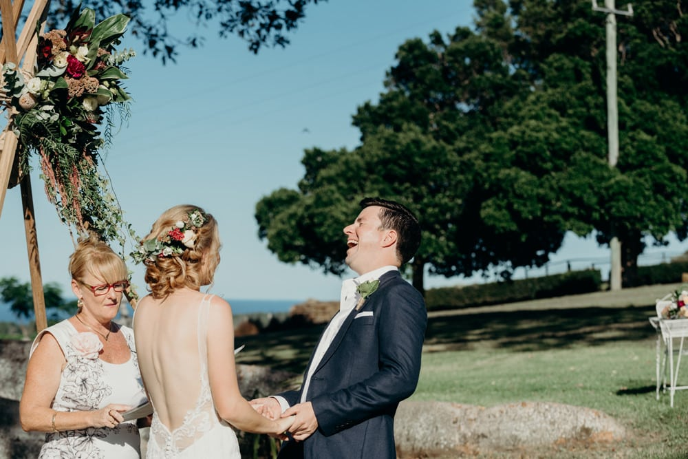 Groom laughing during Vows at Byron Bay wedding by Cloud Catcher Studio