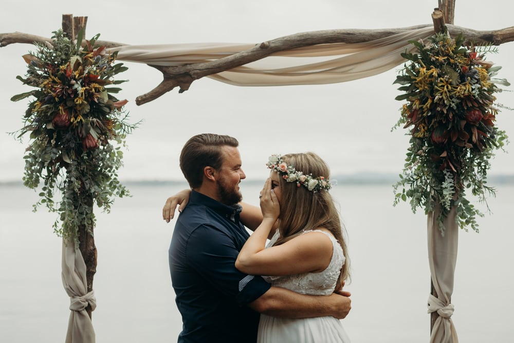 Candid photo of Bride and Groom under flower arbour by the lake Noosa Springs Resort Wedding by Cloud Catcher Studio