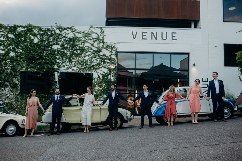 Bridal party with retro cars outside LighspaceBrisbane wedding by Cloud Catcher Studio