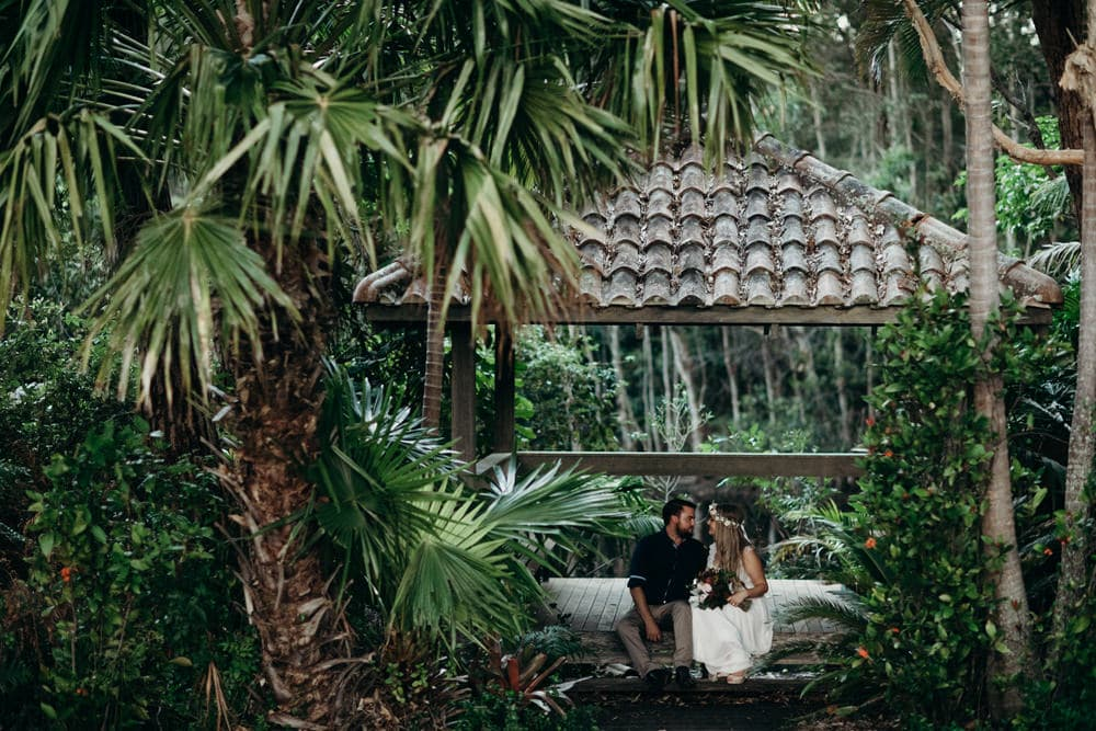Bride and groom sitting in a rainforest hut Noosa Springs Resort Wedding by Cloud Catcher Studio