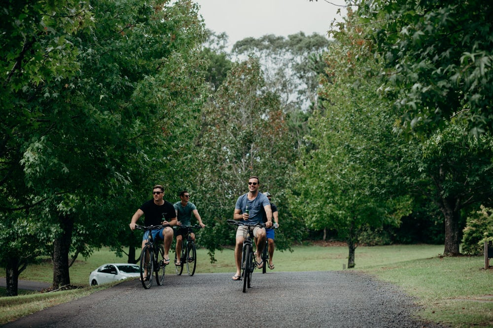 Candid photo of groom and his groomsmen riding bikes at Spicers Clovelly Estate Wedding by Cloud Catcher Studio